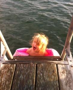 Lill-Emma känner på vattnet med tårna. Kallt!