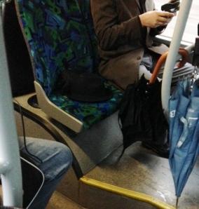 """""""Min hatt och mina handskar behöver ett eget säta trots att bussen är full av gfol som står. För säkerhets skull spärrar jag av med mitt blöta paraply."""""""