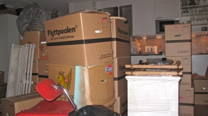 Lådor, möbler och säckar i kaosartad mix. Bild tagen från soffan.