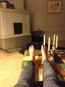 Kakelugn, fårskinn på golvet, mörkröda tånaglar och nya löparbrax.